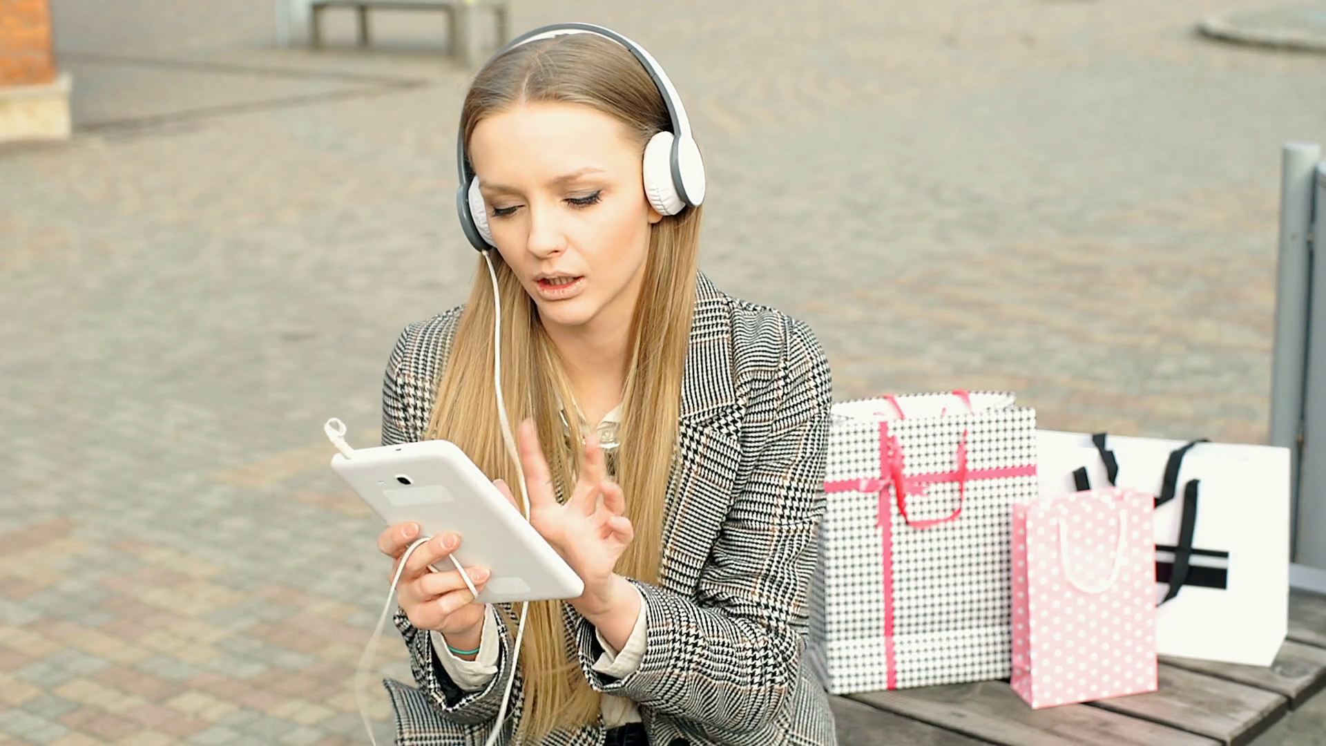 videoblocks-stylish-girl-whistles-while-listening-music-on-the-bench-after-shopping_h0g49kdsnl_thumbnail-full01
